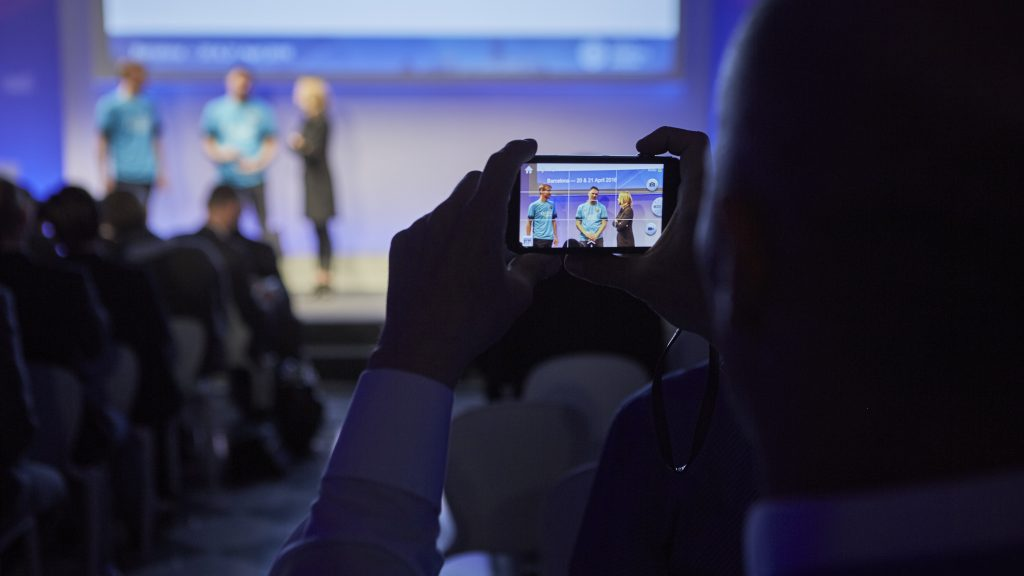 Attendee taking a photo of stage presentation at Digital Insurance Agenda (DIA) Barcelona 2016