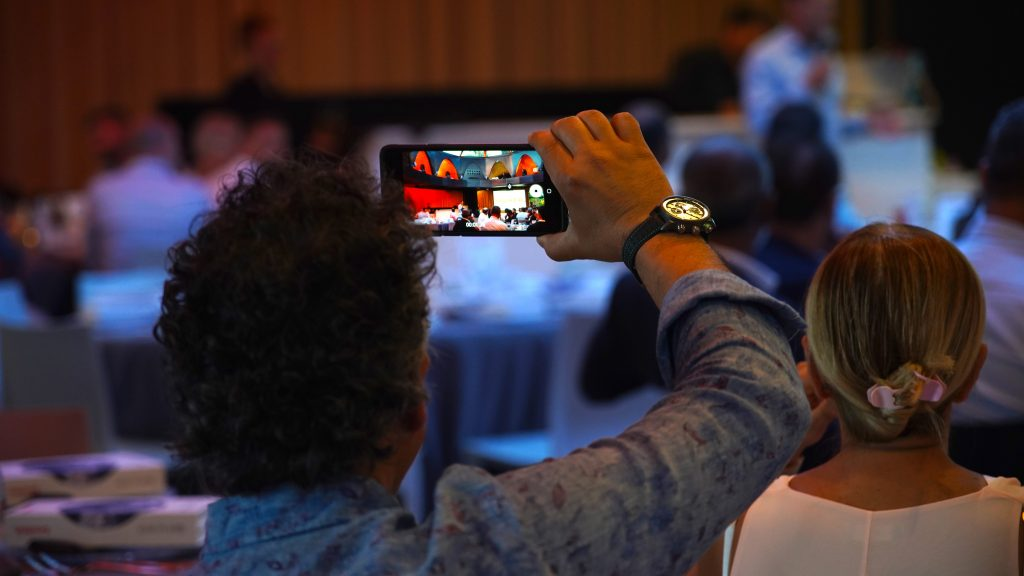 Event attendee taking a photo of a CEO presentation